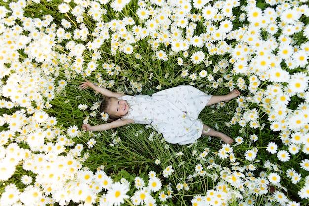 Mała dziewczynka leży na ziemi w kwiatach stokrotek