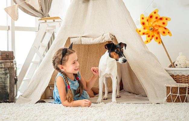 Mała dziewczynka leży w wigwamie z psem foksterier w jasnym pokoju