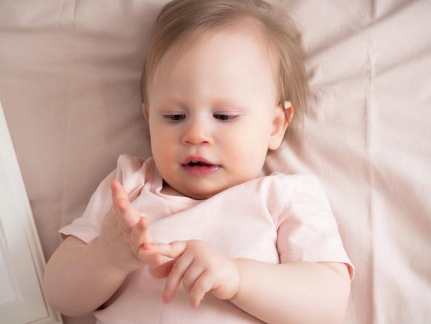 Mała dziewczynka liczy palce, zbliżenie. portret pięknej dziewczyny światła w odcieniach różu. wiek dziecka jeden rok.