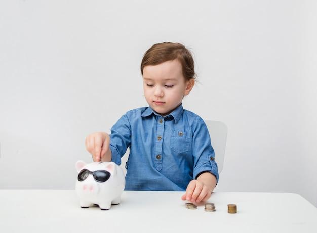 Mała dziewczynka liczy pieniądze i wkłada je do skarbonki. kryzys. ekonomia.