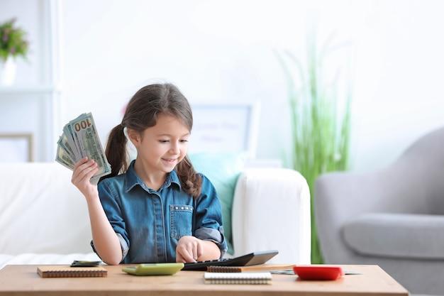 Mała dziewczynka liczy pieniądze przy stole w pomieszczeniu