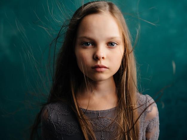Mała dziewczynka luźne włosy zbliżenie zielone tło emocje depresja