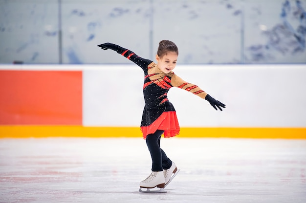 Mała dziewczynka łyżwiarka figurowa w pięknej czarno-czerwonej sukience na łyżwach na krytym lodowisku