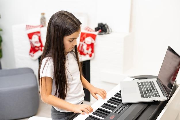 Mała dziewczynka ma lekcję online z nauczycielem na temat gry na pianinie w czasie świąt bożego narodzenia