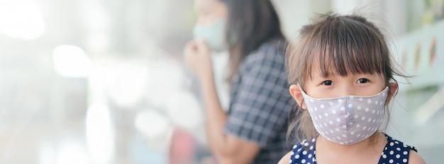 Mała dziewczynka ma maskę z tkaniny, która chroni się przed koronawirusem, nowym normalnym stylem życia po wybuchu covid-19