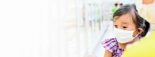 Mała dziewczynka ma maskę z tkaniny, która chroni się przed koronawirusem w banerie w supermarkecie