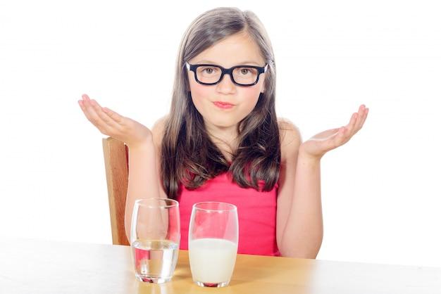 Mała dziewczynka ma wybór między szklanką wody a szklanką mleka na białym tle