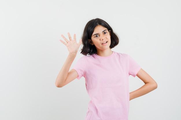 Mała dziewczynka macha ręką, aby się pożegnać w różowy t-shirt widok z przodu.