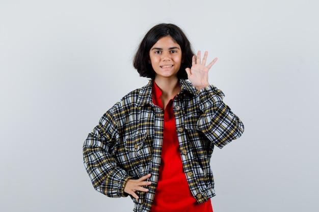 Mała dziewczynka macha ręką na powitanie w koszuli, widok z przodu kurtki.