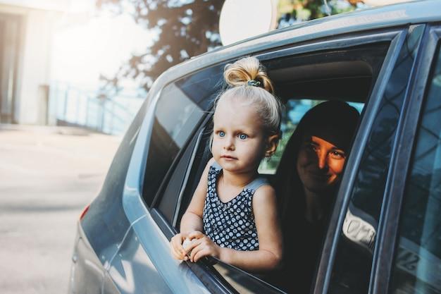 Mała dziewczynka malucha wygląda przez okno samochodu z mamą