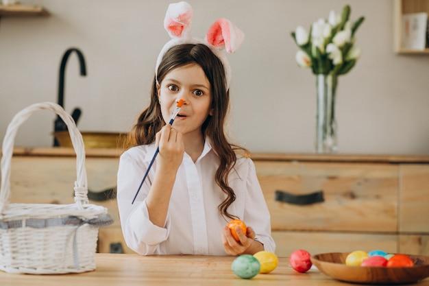 Mała dziewczynka maluje jajka dla easter