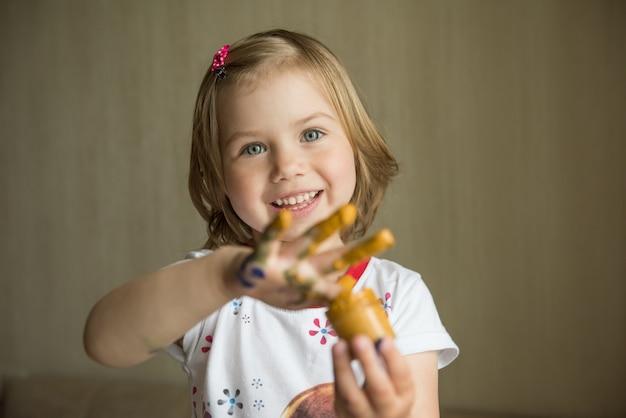Mała dziewczynka maluje jej palcami. selektywne ustawianie ostrości