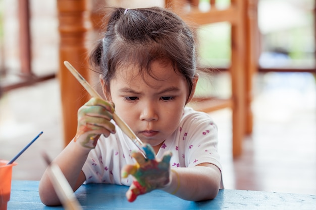 Mała dziewczynka maluje jej rękę