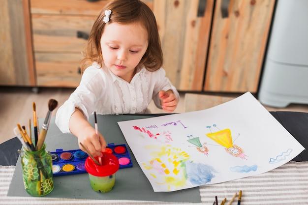 Mała dziewczynka maluje matki i dziecka na papierze