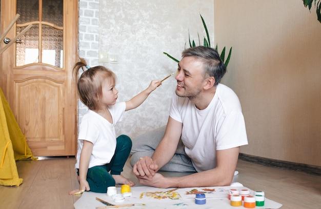 Mała dziewczynka maluje twarz ojca akwarelami. wspólne gry rodzinne