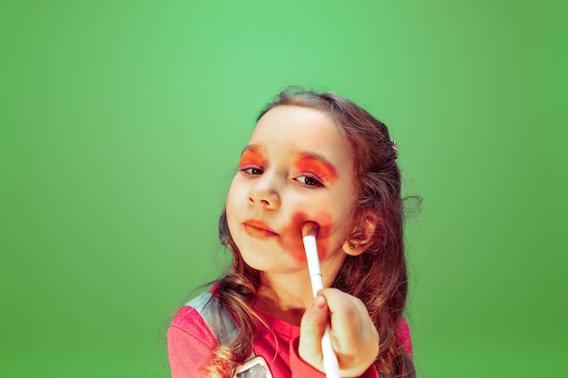 Mała dziewczynka marzy o zawodzie wizażystki. koncepcja dzieciństwa, planowania, edukacji i marzeń.