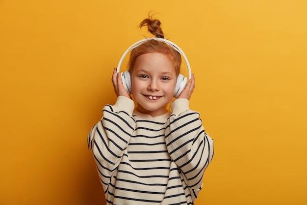 Mała dziewczynka melomanka cieszy się dobrym dźwiękiem w nowych słuchawkach, słucha ulubionej piosenki, bawi się chłodną muzyką, pokazuje mleczne zęby, nosi sweter w paski, odizolowany na żółtej ścianie, ma beztroski nastrój