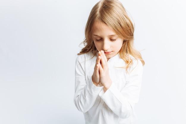 Mała dziewczynka modli się na kolanach do boga, komunia z bogiem, słodka i piękna