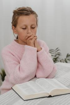 Mała dziewczynka modli się w domu z biblią