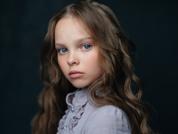 Mała dziewczynka modna fryzura pozowanie ciemne tło studio
