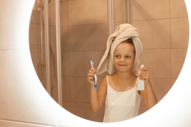 Mała dziewczynka myje zęby w łazience, patrząc na swoje odbicie w lustrze, ubrana w białą koszulkę i owinęła włosy ręcznikiem, trzymając w rękach szczoteczkę i pastę do zębów.
