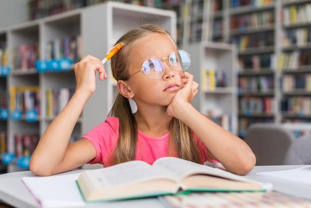 Mała dziewczynka myśli o tym, jak rozwiązać swoją pracę domową