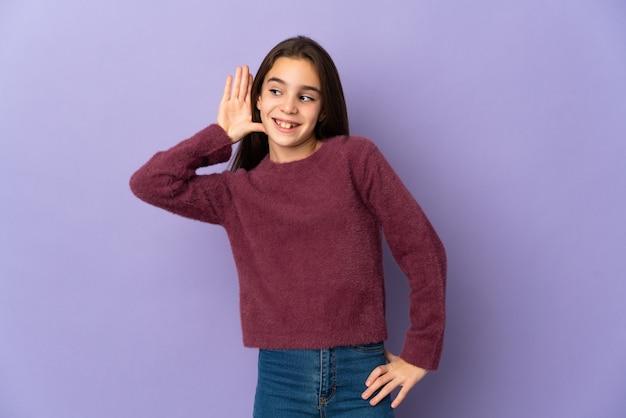 Mała dziewczynka na białym tle na fioletowym tle słuchając czegoś, kładąc rękę na uchu