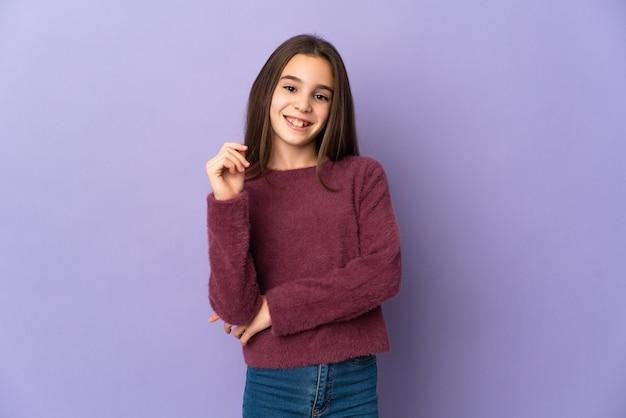 Mała dziewczynka na białym tle na fioletowym tle, śmiejąc się