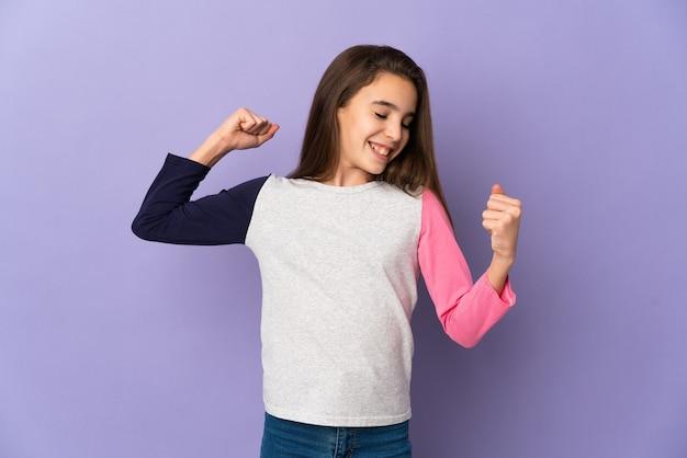 Mała dziewczynka na białym tle na fioletowym tle świętuje zwycięstwo
