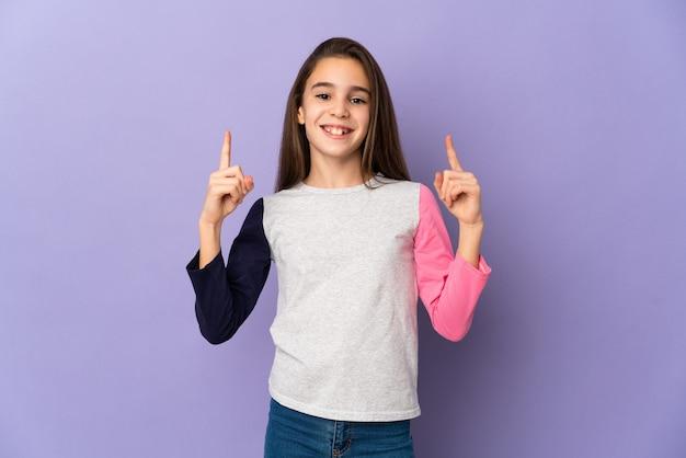 Mała dziewczynka na białym tle na fioletowym tle, wskazując na świetny pomysł