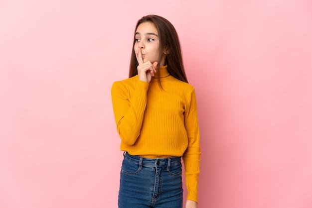 Mała dziewczynka na białym tle na różowej ścianie przedstawiający znak gestu ciszy wkładając palec do ust