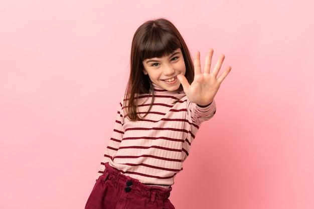 Mała dziewczynka na białym tle na różowym tle, licząc pięć palcami
