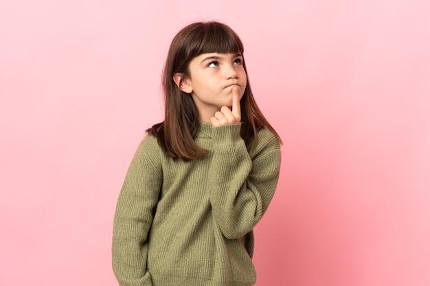 Mała dziewczynka na białym tle na różowym tle, mając wątpliwości, patrząc w górę