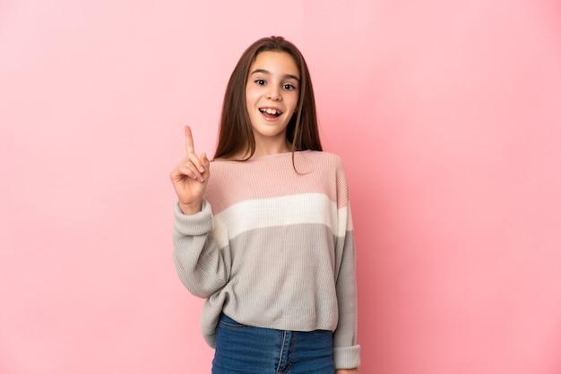 Mała dziewczynka na białym tle na różowym tle myśli pomysł wskazując palcem w górę