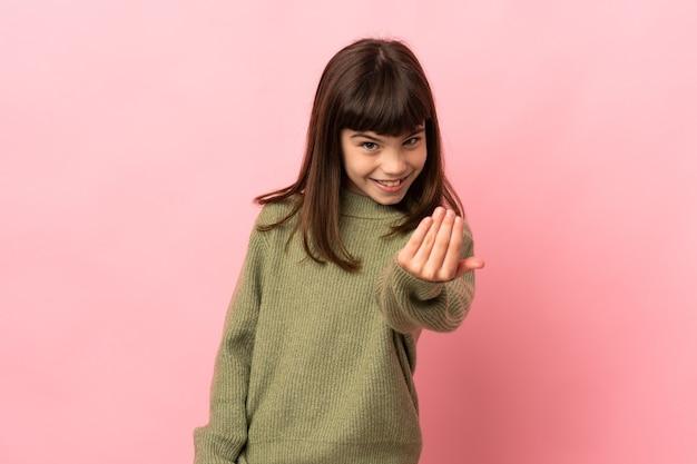 Mała dziewczynka na białym tle na różowym tle, zapraszając do przyjścia z ręką. cieszę się, że przyszedłeś