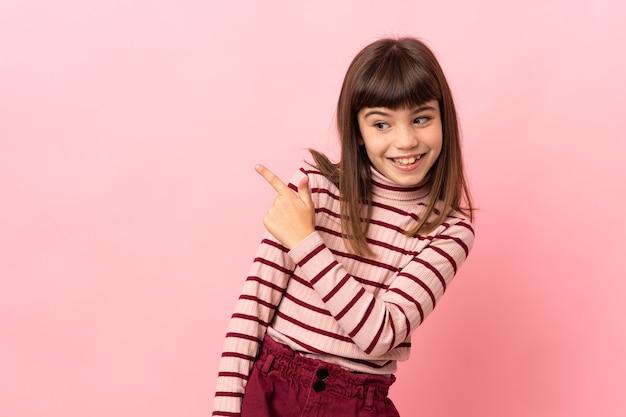 Mała dziewczynka na białym tle na różowym tle zaskoczona i wskazująca strona