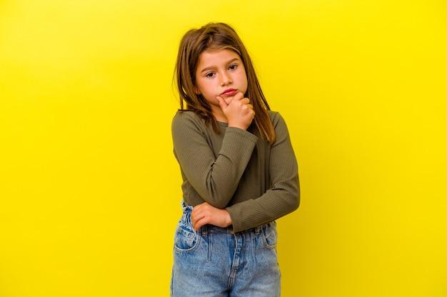 Mała dziewczynka na białym tle na żółtej ścianie myśli i patrząc w górę, jest refleksyjna, kontempluje, ma fantazję