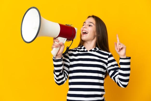 Mała dziewczynka na białym tle na żółtym tle krzyczy przez megafon, aby ogłosić coś w pozycji bocznej