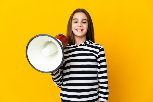 Mała dziewczynka na białym tle na żółtym tle trzyma megafon i dużo się uśmiecha