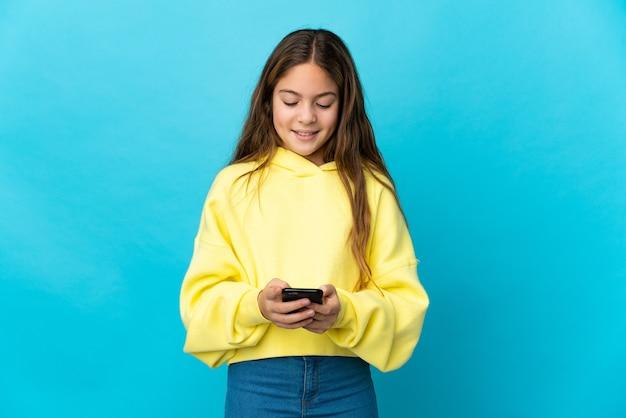 Mała dziewczynka na białym tle niebieski wysyłanie wiadomości z telefonu komórkowego