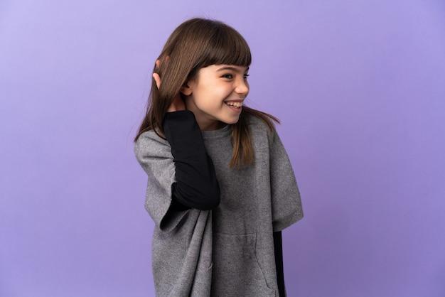Mała dziewczynka na białym tle słuchając czegoś, kładąc rękę na uchu