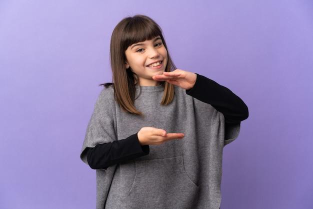 Mała dziewczynka na białym tle trzymając copyspace wyimaginowany na dłoni, aby wstawić reklamę