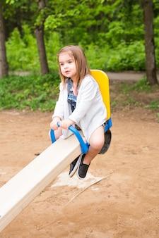Mała dziewczynka na boisku. dziecko bawi się na zewnątrz w lecie.