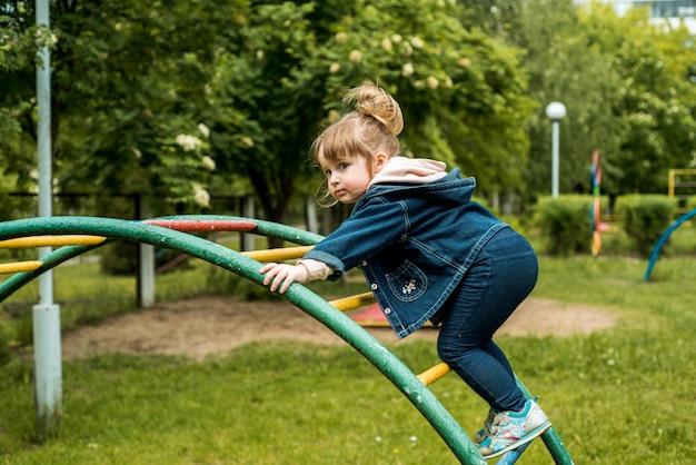 Mała dziewczynka na boisku. szczęśliwy uśmiechnięte dziecko bawiące się na świeżym powietrzu. dziecko się śmieje, emocjonalnie krzyczy, radość i szczęśliwe dzieciństwo.