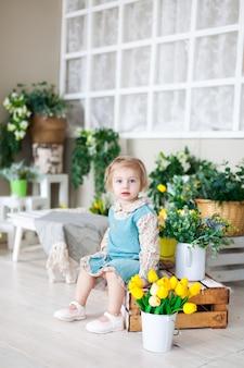 Mała dziewczynka na drewnianej ławce z wiosennymi kwiatami.