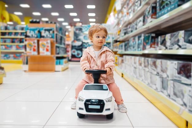 Mała dziewczynka na elektromobilu na półce w sklepie dla dzieci