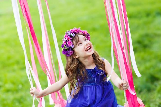 Mała dziewczynka na huśtawce, mała dziewczynka przy parkiem