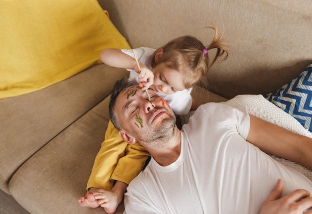 Mała dziewczynka na kanapie starannie maluje twarz ojca podczas wspólnych zabaw rodzinnych
