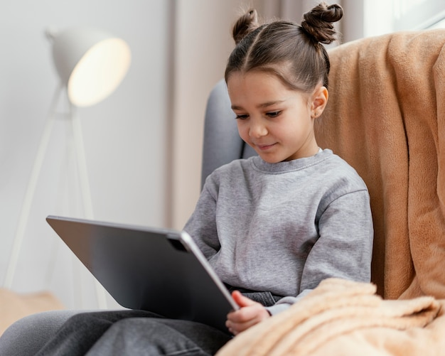 Mała dziewczynka na kanapie za pomocą tabletu