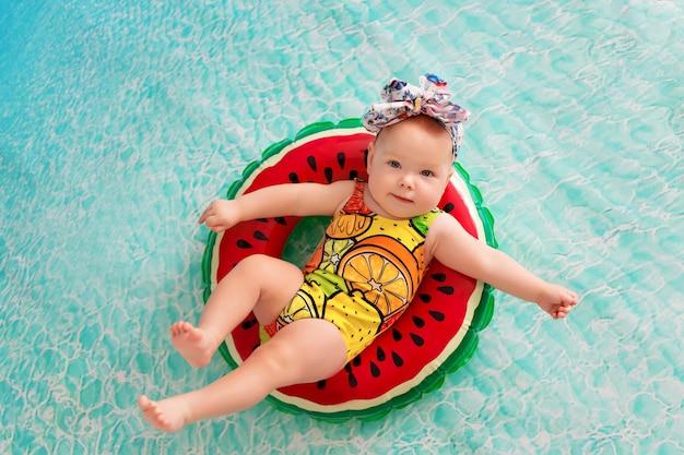 Mała dziewczynka na koło ratunkowe w kształcie arbuza